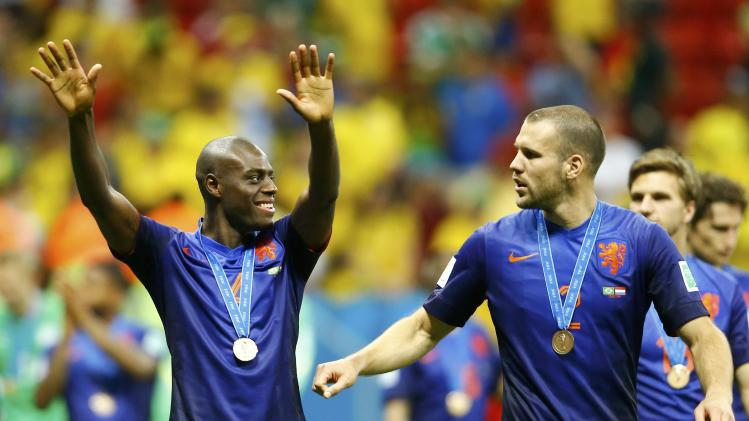 Bruno Martins Indi and Ron Vlaar of the Netherlands celebrate after receiving their medals at the medal ceremony after winning their 2014 World Cup third-place playoff against Brazil at the Brasilia national stadium in Brasilia