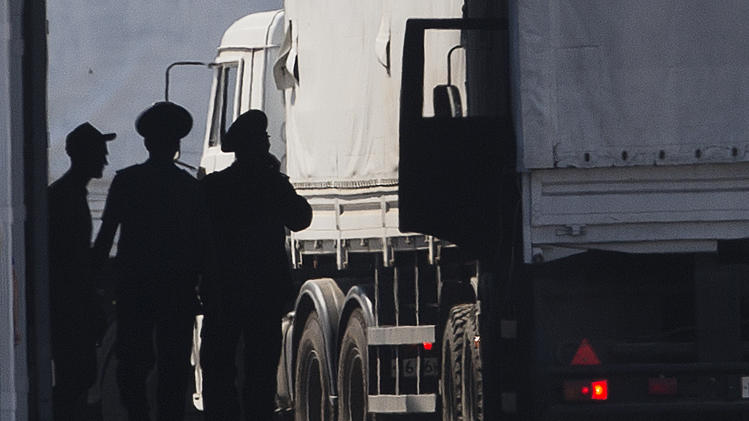 A driver, left, and Russian custom service officers stand near trucks of the Russian aid convoy which are searched at a Russian inspection zone inside a border control point with Ukraine in the Russian town of Donetsk, Rostov-on-Don region, Russia, Friday, Aug. 22, 2014. The first trucks of the Russian aid convoy crossed the Ukrainian inspection zone Friday morning. (AP Photo/Pavel Golovkin)