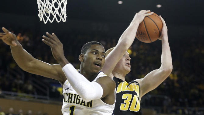 Iowa forward Aaron White (30) grabs a rebound behind Michigan forward Glenn Robinson III (1) during the first half of an NCAA college basketball game at Crisler Arena in Ann Arbor, Mich., Sunday, Jan. 6, 2013. (AP Photo/Carlos Osorio)