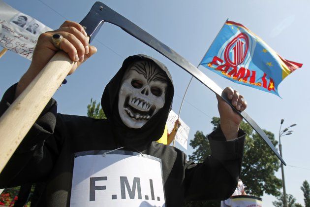 "A man dressed in a costume depicting ""Death"", attends trade unionists' protest in front of Victoria palace, Romania's government headquarters, in Bucharest"