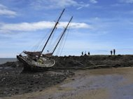 The twin-masted yacht &quot;Patricia Mary&quot; is shown washed up January 28, 2013 on Baraga Beach in Bundaberg after the passing of tropical cyclone Oswald. A mammoth clean-up operation began in Australia&#39;s flood-hit northeast Wednesday after waters began to recede, as the death toll from storms reached six and thousands of homes were left swamped