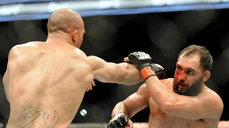Johny Hendricks blocks a punch from Robbie Lawler during a UFC 171 mixed martial arts welterweight title bout, Saturday, March 15, 2014, in Dallas. Hendricks won by decision
