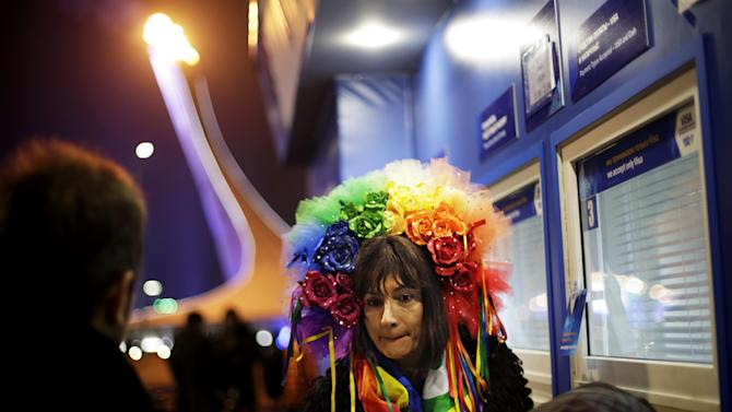 Vladimir Luxuria, a former Communist lawmaker in the Italian parliament and prominent crusader for transgender rights, waits to receive her ticket at a box office for a women's ice hockey match as the Olympic flame burns in the background at the 2014 Winter Olympics, Monday, Feb. 17, 2014, in Sochi, Russia. Luxuria was soon after detained by police upon entering the Shayba Arena to attend the women's ice hockey match. (AP Photo/David Goldman)