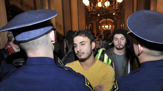 State Police block  protesters outside the Senate chamber  at the State Capitol Building in downtown Lansing, Mich. Thursday, Dec. 6, 2012. Eight people were arrested for resisting and obstructing when they tried to push past two troopers guarding the Senate door, state police Inspector Gene Adamczyk said. The Capitol was temporarily closed because of safety concerns. (AP Photo/The State Journal, Rod Sanford)