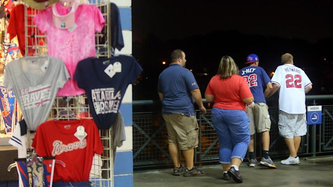 Baseball fans look over a railing at Turner Field near the scene where a man fell 60 feet from the upper deck Monday Aug. 12, 2013. Atlanta police spokesman John Chafee confirmed the death of the man, whose name has not been released. The man fell during Monday night's game between the Atlanta Braves and Philadelphia Phillies. (AP Photo/Atlanta Journal Constitution, Curtis Compton) MARIETTA DAILY OUT, GWINNETT DAILY POST OUT) LOCAL TV OUT (WXIA, WGCL, FOX 5).