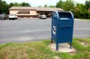 This photo taken July 27, 2012 shows a mailbox outside a US Post Office in Lawrence, Mich. The U.S. Postal Service is bracing for a first-ever default on billions in payments due to the Treasury, adding to widening uncertainty about the mail agency's solvency as first-class letters plummet and Congress deadlocks on ways to stem the red ink. (AP Photo/Robert Ray)