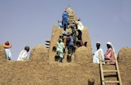<p>Local residents restoring the City of 333 Saints' Great Djingareyber Mosque in Timbuktu in 2006. The international community on Tuesday weighed options to help embattled Mali save its north from Islamist fighters who have smashed ancient shrines in Timbuktu and rigged another city with landmines.</p>