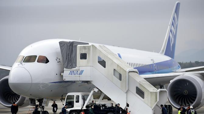 Officials examine an All Nippon Airways 787 that landed at Takamatsu airport in Takamatsu, western Japan, on the day before after leaking electrolyte from a main battery located in an electrical room below the cockpit, Thursday, Jan. 17, 2013. Japan's two biggest airlines and the U.S. aviation agency grounded more than half the Boeing 787s in use around the world after the emergency landing of one of the jets exposed a battery fire risk in the technologically advanced aircraft. (AP Photo/Kyodo News)  JAPAN OUT, MANDATORY CREDIT, NO LICENSING IN CHINA, HONG KONG, JAPAN, SOUTH KOREA AND FRANCE