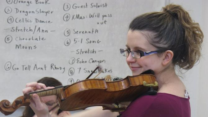 In this Nov. 17, 2012, photo, conductor Gabrielle Whitfield practices the violin with the Hiland Mountain Correctional Facility Orchestra in Eagle River, Alaska. After serving a 14-year sentence for murder, Sarah Jane Coffman, a founding member of the women's string orchestra at the prison in 2003, will debut as a citizen member when the two annual holiday concerts are held Dec. 8, 2012. (AP Photo/Mark Thiessen)