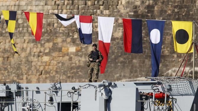 A Royal Marine patrols the deck of the Royal Navy's HMS Bulwark amphibious assault ship docked in a harbour during the Commonwealth Heads of Government Meeting in Valletta