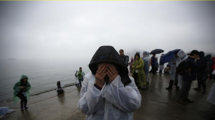 "A family member of missing passengers who were on the South Korean ferry ""Sewol"" which sank in the sea off Jindo covers her face as she cries at a port in Jindo"