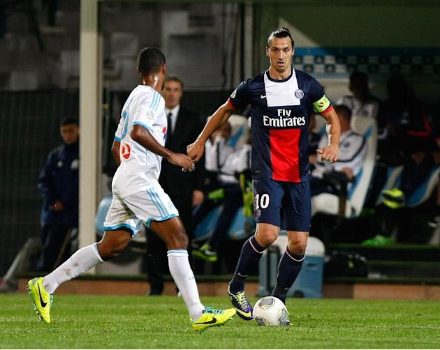 Paris Saint Germain's Swedish forward Zlatan Ibrahimovic, right, challenges for the ball with Marseille's Togolese midfielder Jacques-Alaixys Romao, during their League One soccer match, at the Velodr
