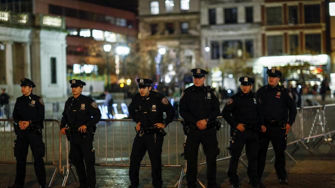 New York Police Department officers stand guard as protesters shout slogans against the law as they rally in New York