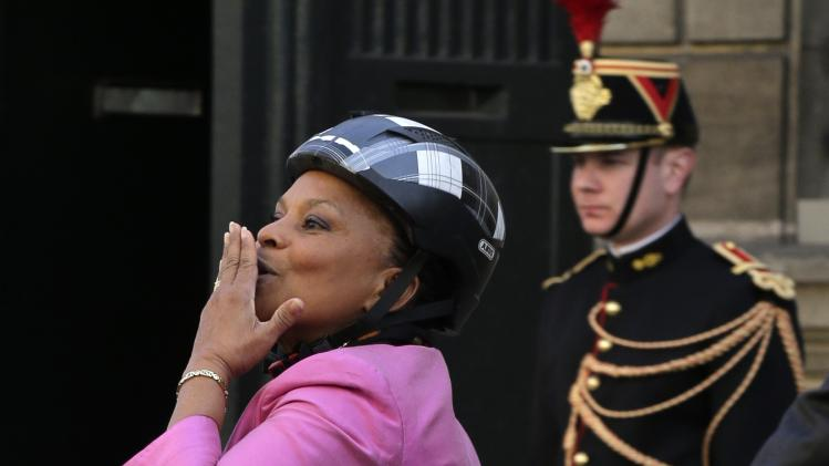 French Justice Minister Christiane Taubira blows a kiss as she leaves the Elysee Palace on a bicycle after a meeting in Paris
