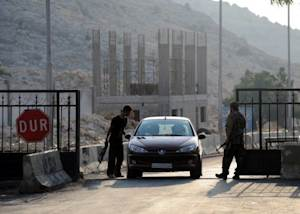 Syrian gunmen open the Bab al-Hawa border gate between Turkey and Syria on July 21