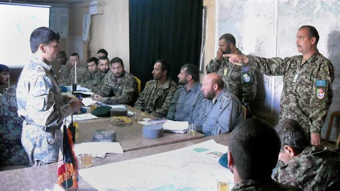 In this March 25, 2013, photo, Afghan Maj. Mahboob, who goes by one name, of the Afghan national army's 2nd Brigade, 201st Corps, leaping to his feet and gesturing across the table for emphasis while arguing with Afghan colleagues about a future operation at the Afghan army's Sarkani Base, next to Forwarding Operating Base Joyce, in Kunar province, in eastern Afghanistan. U.S. commanders trying to hand off war-fighting responsibility by the end of 2014 are encouraged by the uneven yet steady progress of fledgling Afghan security forces. (AP Photo/Kim Dozier)