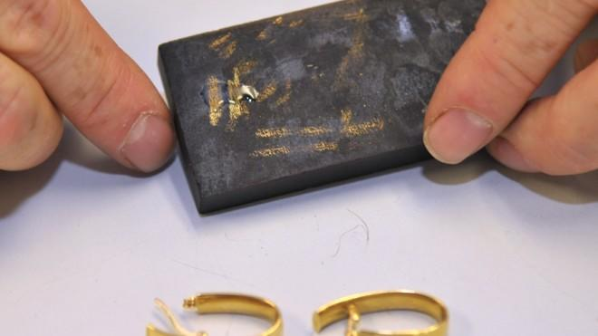 A pawn shop employee tests the karat amount in a pair of gold earrings.