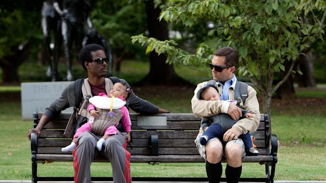 "This undated image provided by Lionsgate shows Chris Rock, left, and Tom Lennon with children in a scene from the movie ""What to Expect When You're Expecting.""  A growing league of dads are staying home, at least part-time. Some at-home dads, those by choice or pushed out of the job market, said they've endured some snark by their working brethren, but they consider it more of a dad-on-dad discomfort than a serious divide. (AP Photo/Lionsgate, Melissa Moseley)"