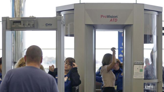 In this Wednesday, Oct. 24, 2012 photo, passengers are scanned at a Terminal C security checkpoint at Logan Airport in Boston using a millimeter wave body scanner, which produces a cartoon-like outline rather than naked images of passengers produced by a similar machine using X-rays. The Transportation Security Administration is deploying more of the millimeter wavemachines at seven major U.S. airportswhere the agency is removing all of the full-body X-ray scanners that have been criticized by privacy advocates. (AP Photo/Charles Krupa)