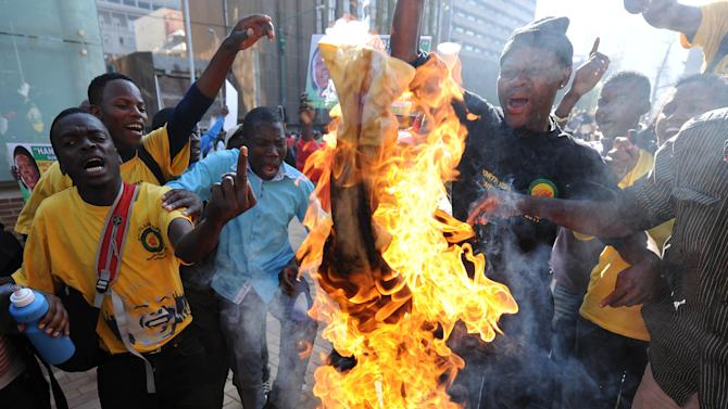 African National Congress Youth League (ANCYL) supporters burn a party T-shirt with a portrait of South African president  Jacob Zuma in downtown Johannesburg, Tuesday, Aug. 30, 2011 as they protest at the start of a disciplinary hearing against their leader Julius Malema. Malema could be expelled or suspended from the ANC for bringing the party into disrepute with their calls for the overthrow the governemnt of neighboring Botswana.  (AP Photo)