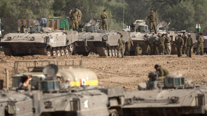Israeli soldiers work on their a tanks in a staging ground near the border with Gaza Strip, southern Israel, Friday, Nov. 16, 2012. Fierce clashes between Israeli forces and Gaza militants are continuing for the third day.(AP Photo/Ariel Schalit)