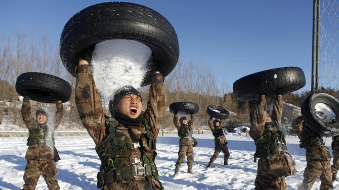 PLA soldiers pour snow from a tyre onto their head during a training session in Heihe