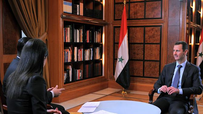 """This photo released by the Syrian official news agency SANA on Wednesday, April 17, 2013, shows Syrian President Bashar Assad, right, during an interview broadcast on Syrian state television in Damascus, Syria. Syria's president accused the West on Wednesday of backing al-Qaida in his country's civil war, warning it will pay a price """"in the heart"""" of Europe and the United States as the terror network becomes emboldened. Bashar Assad also lashed out at Jordan for allowing """"thousands"""" of fighters to enter Syria through its borders. The rare TV interview comes as the embattled president's military is fighting to reverse rebel advances, with a rocket attack killing at least 12 people in a central village on Wednesday. (AP Photo/SANA)"""