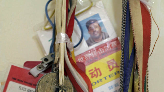 Maria Victoria Gil, mother of swordsman Elvis Gregory, shows her son's Olympic medal that is displayed in her home, in Havana, Cuba, Friday, Nov. 16, 2012. Gregory, an Olympic silver medalist, who defected from the Cuban team at a tournament in Lisbon in 2002, hopes to return to Cuba next year so he can finally meet his only child, a 10-year-old girl who was only 15 days old when he abandoned his country.  New migratory laws have now made it possible for high-profile defectors once considered deserters or traitors to return to the homeland they abandoned. The new rules could potentially affect many leading cultural and athletic figures, from musicians and doctors to ballet dancers. (AP Photo/Franklin Reyes)