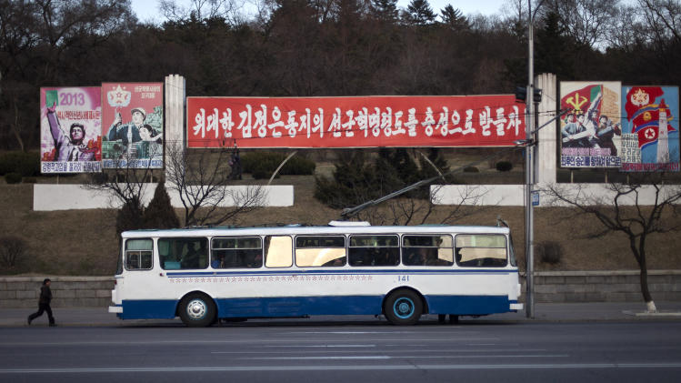 """A woman runs on her way to catch a trolley bus in Pyongyang, North Korea, Thursday, April 11, 2013. A sign behind the bus reads: """"Let's Uphold the Military First Revolutionary Leadership of the Great Comrade Kim Jong Un With Loyalty."""" (AP Photo/Alexander F. Yuan)"""