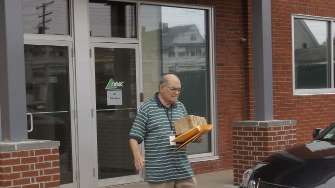 An unidentified man carries packages out of New England Compounding in Framingham, Mass., Thursday, Oct. 4, 2012. An outbreak of a rare and deadly form of fungal meningitis that has killed 4 people and sickened another 26 in five states is believed to have been traced back to a steroid manufactured by the New England Compounding Center. Investigators, though, say they are still trying to confirm the source of the infection. (AP Photo/Stephan Savoia)