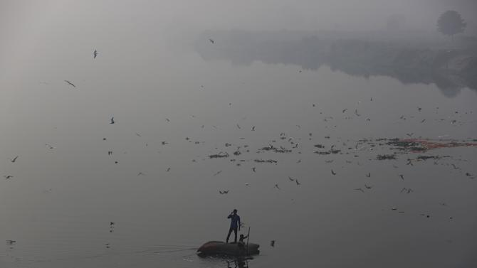 Boys look for recyclable items in the waters of river Yamuna on a smoggy morning in New Delhi