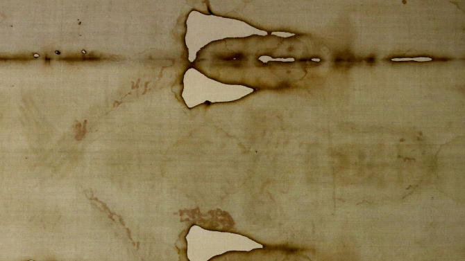 A detail of the Holy Shroud, the 14 foot-long linen revered by some as the burial cloth of Jesus, is seen as it goes on display during a preview for the press at the Cathedral of Turin, Italy, Saturday, April 18, 2015. The long linen with the faded image of a bearded man, that is the object of centuries-old fascination and wonderment, will be on display for the public from April 19 to June 24, 2015. Pope Francis said he is planning to visit the Holy Shroud during a a pilgrimage to Turin next June 21, 2015. (AP Photo/Antonio Calanni)
