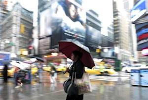 A woman walks through Time Square during a rain storm in New York