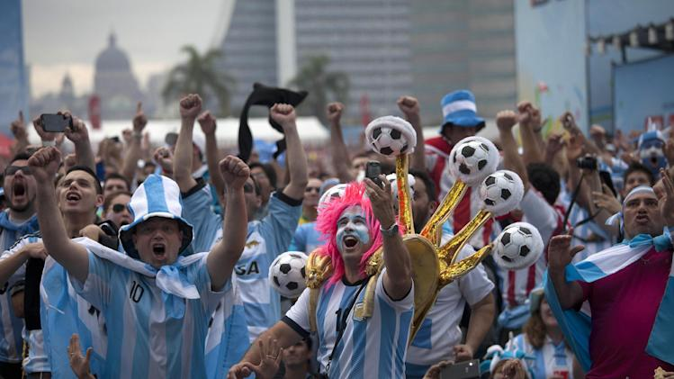 Argentine soccer fans decked out in their national team's colors, celebrate after watching their side score a goal, via a live telecast of the World Cup group F match between Argentina and Nigeria, inside the FIFA Fan Fest area, in Porto Alegre, Brazil, Wednesday, June 25, 2014. (AP Photo/Dario Lopez-Mills)