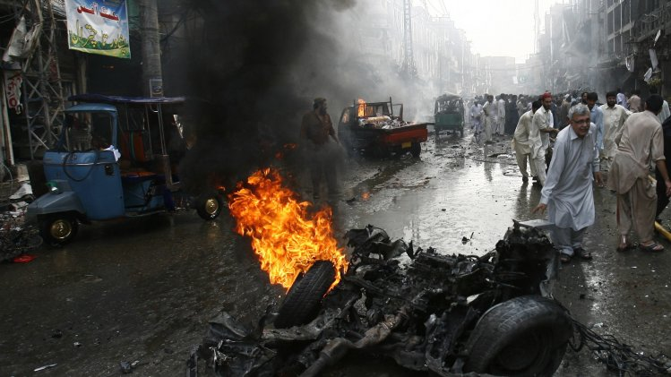 Security officials, rescue workers and residents gather at the site of a bomb attack in Peshawar