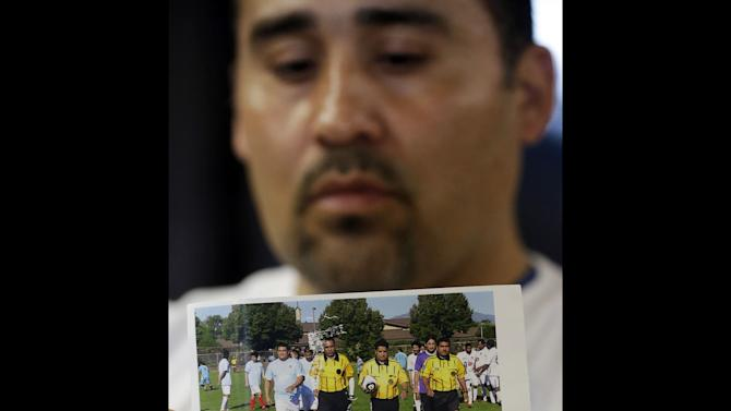 FILE - In this Thursday, May 2, 2013 file photo, Jose Lopez points to an undated photo of Ricardo Portillo, center, his brother-in-law, following a news conference, at Intermountain Medical Center, in Murray, Utah. Portillo, a 46-year-old soccer referee who was punched by a teenage player during a game and later slipped into a coma died Saturday night, May 4, 2013, police said. (AP Photo/Rick Bowmer, File)