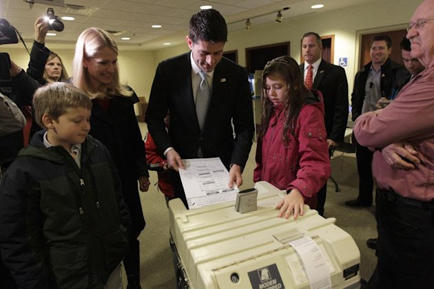 Republican vice presidential candidate, Rep. Paul Ryan, R-Wis., casts his ballot as his wife Janna, son Charlie, left and daughter Liza watch, Tuesday, Nov. 6, 2012 at the Hedberg Public Library in Ja