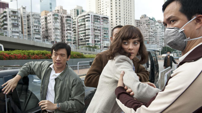 "In this image released by Warner Bros. Pictures, Chin Han, left, and Marion Cotillard are shown in a scene from the film ""Contagion."" (AP Photo/Warner Bros. Pictures, Claudette Barius)"