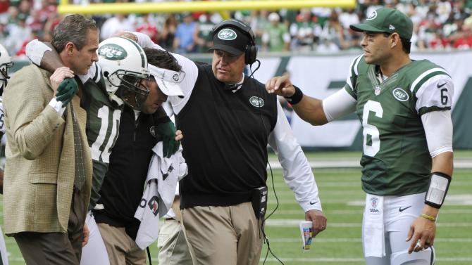 New York Jets wide receiver Santonio Holmes (10) is helped off the field as New York Jets head coach Rex Ryan, second from right, and  Mark Sanchez (6) show their support during the second half of an NFL football game against the San Francisco 49ers Sunday, Sept. 30, 2012, in East Rutherford, N.J. The Jets lost the game 34-0. (AP Photo/Bill Kostroun)
