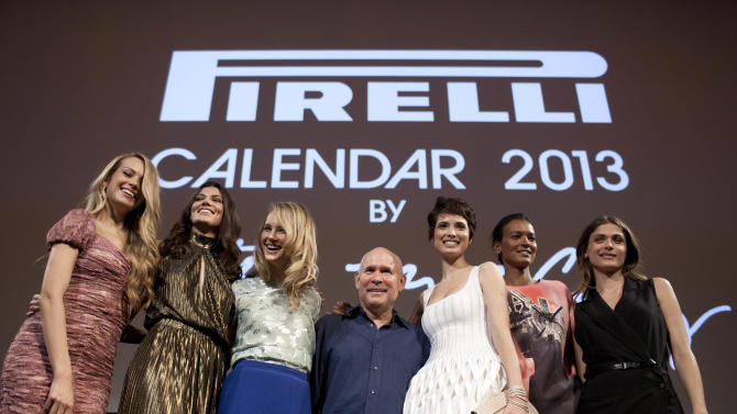 Photographer Steve McCurry, center poses for a photo with supermodels Petra Nemcova, from left to right, Summer Rayne Oakes, Kyleigh Kuhn, Hanaa Ben Abdesslem, Liya Kebede, and Elisa Sednaoui at a press conference promoting the 2013 Pirelli Calendar in Rio de Janeiro, Brazil, Tuesday, Nov. 27, 2012. (AP Photo/Felipe Dana)