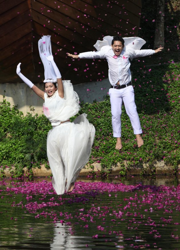 Thai groom Prasit Rangsiyawong and his bride Varuttaon Rangsiyawong jump in a pond during a wedding ceremony in Prachin Buri province