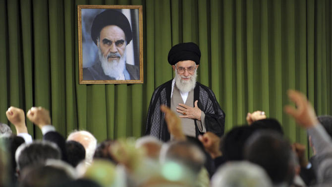 In this photo released by the official website of the Iranian supreme leader's office, Iranian supreme leader Ayatollah Ali Khamenei, places his hand on his heart as a gesture of respect to the lawmakers, foreground, as some of them clench their fists while chanting slogans, at the start of their meeting, in Tehran, Iran, Sunday, May 29, 2011. A picture of the late revolutionary founder Ayatollah Khomeini hangs at rear. (AP Photo/Office of the Supreme Leader)  EDITORIAL USE ONLY  NO SALES