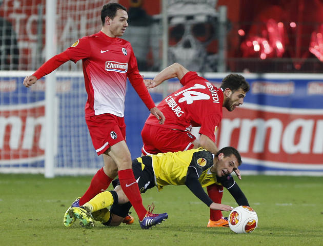 Freiburg's Admir Mehmedi of Switzerland, center, and Freiburg's Nicolas Hoefler, left, and Sevilla's Sebastian Cristoforo challenge for the ball during a Group H Europa League match betwee