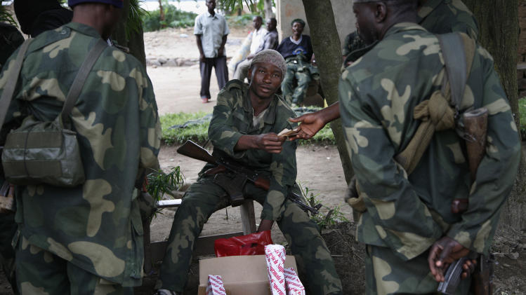 Congolese government soldiers (FARDC) sell cigarettes  in Minova, which is under their control Sunday  Nov. 25, 2012.  Government troops remain in Minova, 25 kilometers (15 miles) south of Sake, following a failed attack on M23 last Thursday.Regional leaders meeting in Uganda called for an end to the advance by M23 rebels toward Congo's capital, and also urged the Congolese government to sit down with rebel leaders as residents fled some towns for fear of more fighting between the rebels and army.(AP Photo/Jerome Delay)