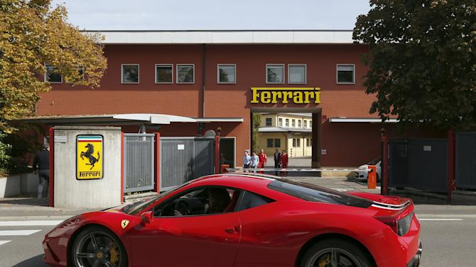 A Ferrari sport car goes past in front of Ferrari's factory in Maranello