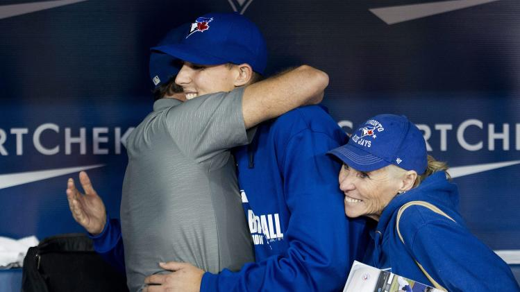 Toronto Blue Jays pitcher Aaron Sanchez, center, hugs his father Mike Shipley, left, as his mother Lynn Shipley, right, reacts after making his major league debut against the Boston Red Sox during baseball game action in Toronto, Wednesday, July 23, 2014. (AP Photo/The Canadian Press, Nathan Denette)