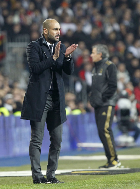 FC Barcelona's coach Pep Guardiola,left, gestures besides Real Madrid's coach Jose Mourinho from Portugal, right, during their quarter finals, first leg, Copa del Rey soccer match at the Santiago Bernabeu stadium in Madrid, Spain, Wednesday, Jan. 18, 2012. (AP Photo/Andres Kudacki)