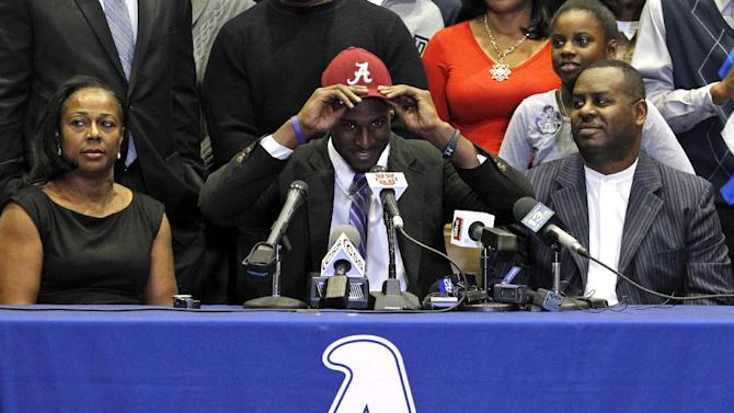 Chenavis Evans, left, and d Allan Evans, right, watch as their son Rashaan Evans dons an Alabama hat as the Auburn High School football player announces that he will attend Alabama during a national signing day ceremony on Wednesday, Feb. 5, 2014, in Auburn, Ala