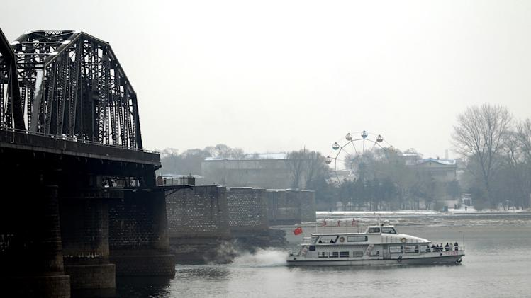 A Chinese tour boat sails past the Friendship Bridge linking between China and North Korea, in Dandong, China Wednesday, Feb. 13, 2013. Defying U.N. warnings, North Korea on Tuesday conducted its third nuclear test in the remote, snowy northeast, taking a crucial step toward its goal of building a bomb small enough to be fitted on a missile capable of striking the United States. (AP Photo/Aritz Parra)