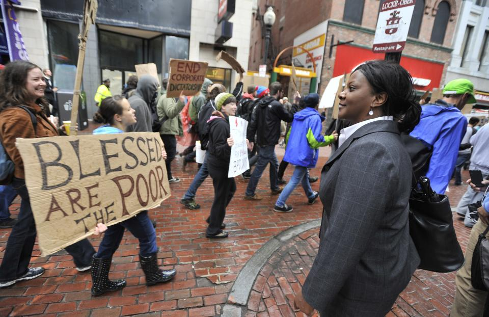 Cheryl Crawford, of Boston, right, watches as marchers with Occupy Boston pass through Downtown Crossing during a demonstration on Monday, Oct. 3, 2011. The group is part of a nationwide grassroots movement in support of the ongoing Wall Street protests in New York. (AP Photo/Josh Reynolds)